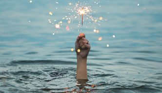 Hand holding sparkler in water